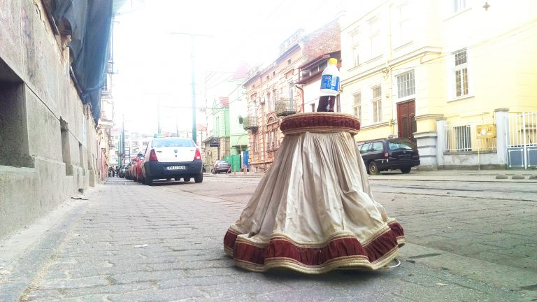 lampshade on the sidewalk with a bottle of Pepsi on top