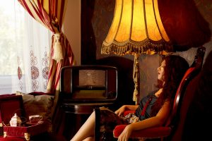 girl relaxing in an armchair at home low lighting vintage interior design old radio lamp warm colors