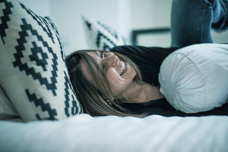 girl laughing in bed black an white pillows being at home happy