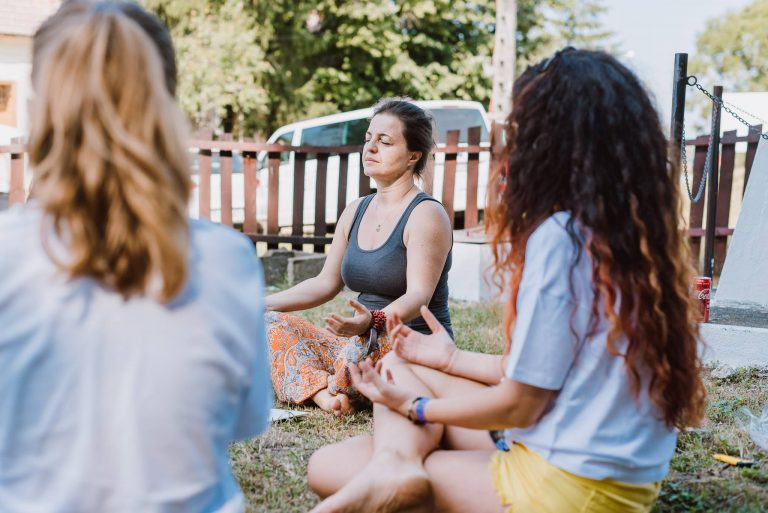 women meditating in nature on the grass relaxed atmosphere