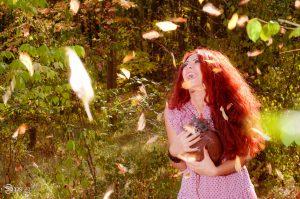 fata roscata rade in padure culori de toamna sepia lampa lanterna fericire bucurie
